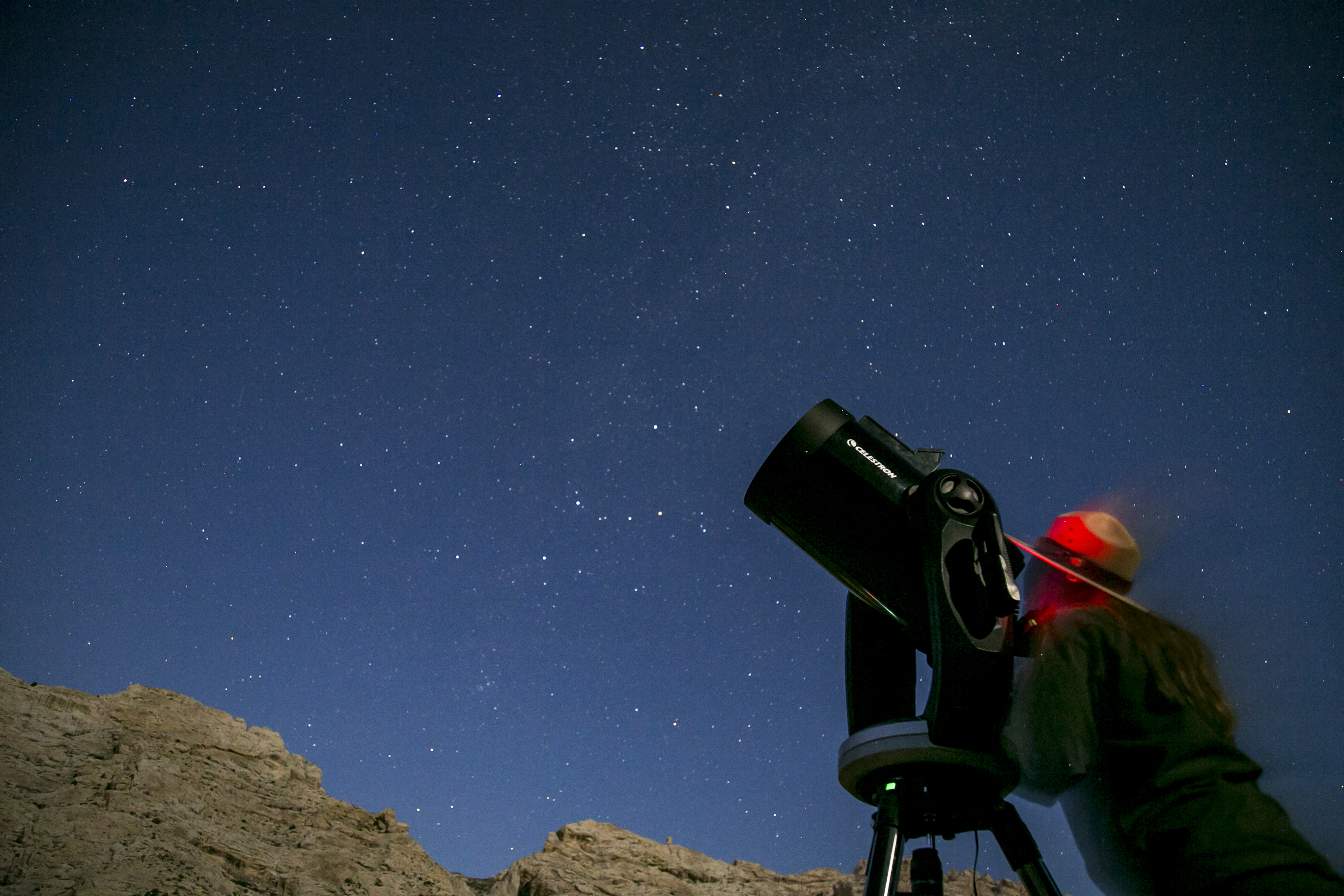 A park ranger looks through a telescope at stars sparkling over the rocks of Split Mountain.