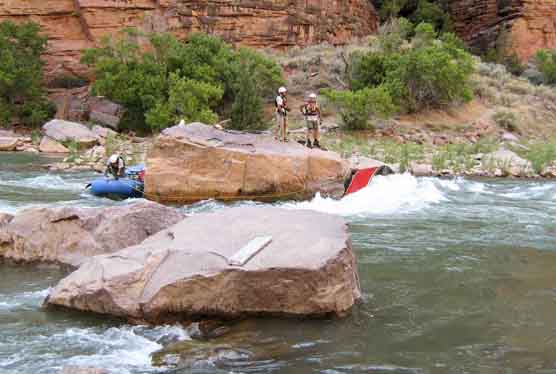 Dinosaur National Monument ranger Doug Ross secures raft to Winnie's Rock, while rangers Phil Dendel and Matt Gilbert discuss safety precautions.