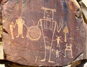 Petroglyphs of human-like figures carved into sandstone that has been stained black.