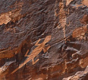 Petroglyphs of two lizards on sandstone stained with desert varnish, a dark coating found on rocks in arid regions.