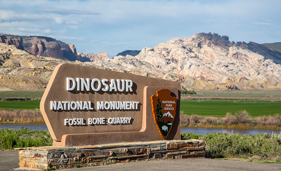 Sign greeting visitors at entrance to monument with mountains in background