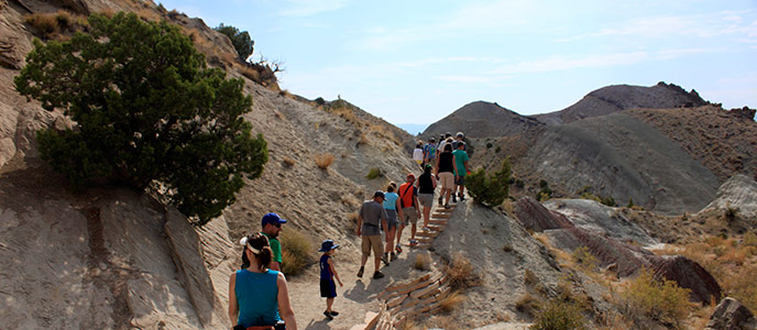 Visitors explore the Fossil Discovery Trail with a park ranger.