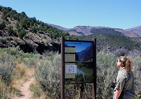 A hiker reads the trailhead sign at the start of the Gates of Lodore Trail.