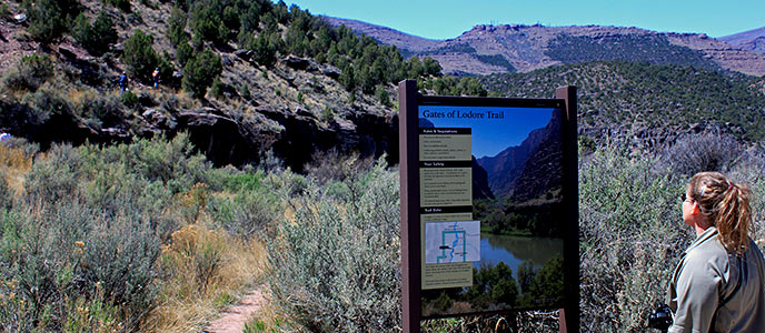 A visitor reads a trailhead sign for the Gates of Lodore trail.