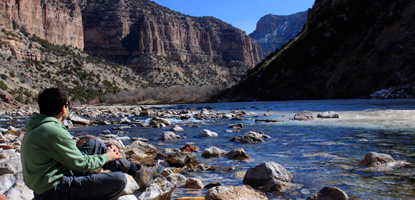A hiker rests along the Green River at Jones Hole.