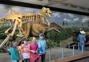 Several young dinosaur enthusiasts pose in front of the Allosaurus reconstruction at the Quarry Exhibit Hall.