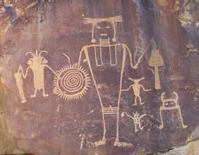 Large petroglyph of human-like figure with trapezoidal body and with several other human-like figures around it.