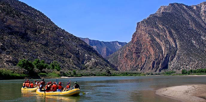A rafting day trip floats towards the upturned rock layers of Split Mountain near Rainbow Park.