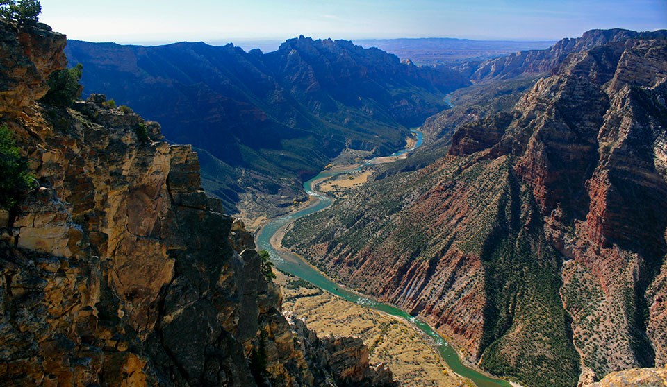 Green colored river flowing in canyon between two mountains made of multi-colored rocks.
