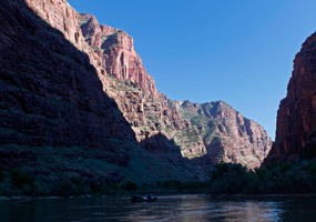 Canyon walls along the Green River dwarf a raft passing in the shadows.