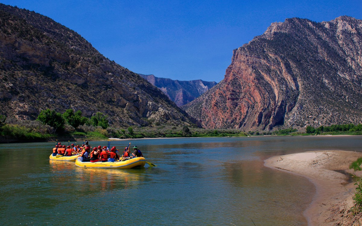 Two yellow rafts filled with people float on a rivers towards large colorful cliffs.
