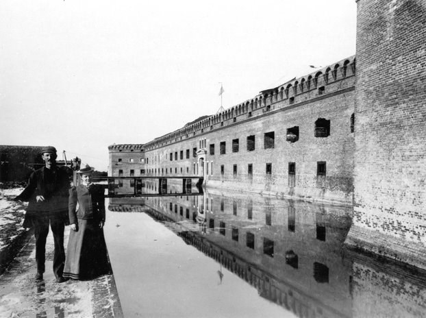 Couple walks along moat wall circa 1899