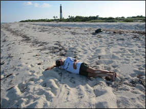Biologist sprawled across the tracks left by a nesting leatherback sea turtle