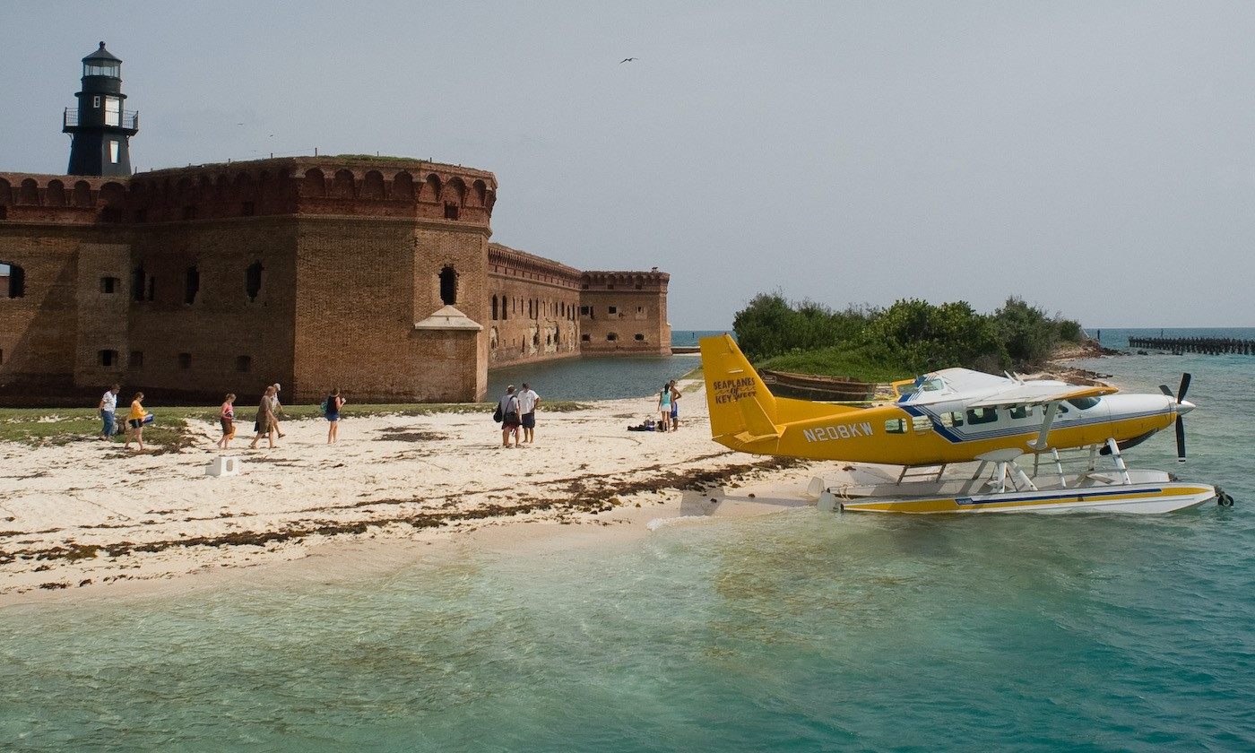 A sea plane sits on the beach as visitors walk toward it with three-story brick fort with harbor lighthouse in the background. Blue-green water in the foreground.