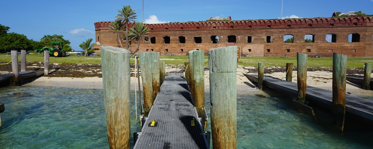A wooden pier around sand and blue ocean waters, with a large brick structure in the background