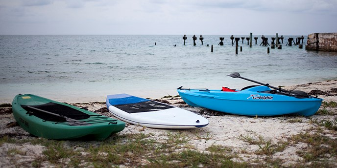 Kayak and paddleboard are parked on the beach.