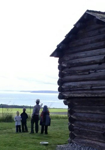 Ranger and kids stand by historic structure and look at the horizon