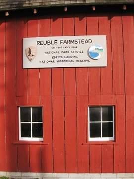 Side of red barn with sign and two windows.