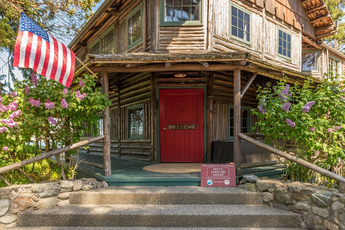 Front door of old log inn with American Flag.