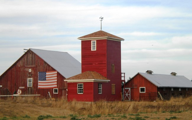Red barn and water tower with American flag.