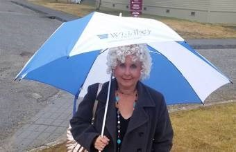 Woman with spiral curly hair holding an umbrella