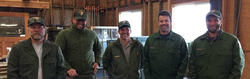 Five men stand in a woodshop wearing park service uniforms