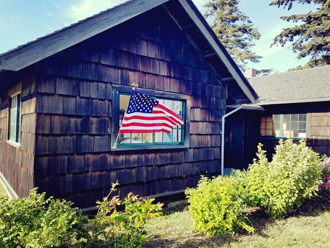 Shingled cottage with American flag flying.