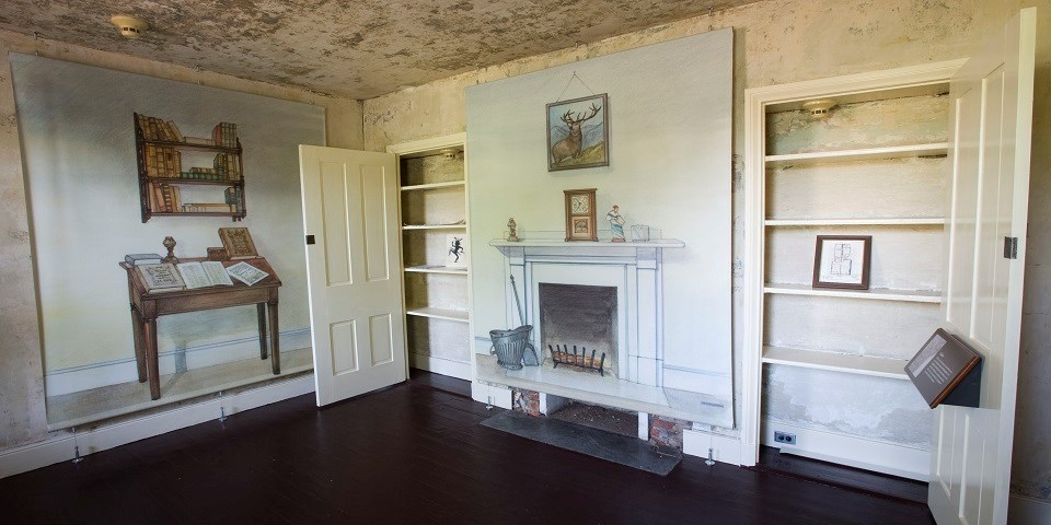 Color photo of a small room with life-size illustrations of a writing desk, bookshelf, and chimney on the walls.