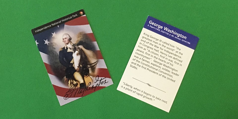 Color photo showing both sides of a trading card - one side shows a painting of George Washington on a white horse and the other side shows text about Washington's life.