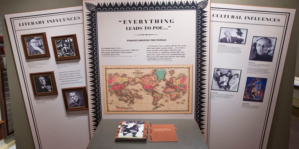 Color photo showing large exhibit signs with an illustrated world map and black and white photos that detail Poe's influence throughout the world.