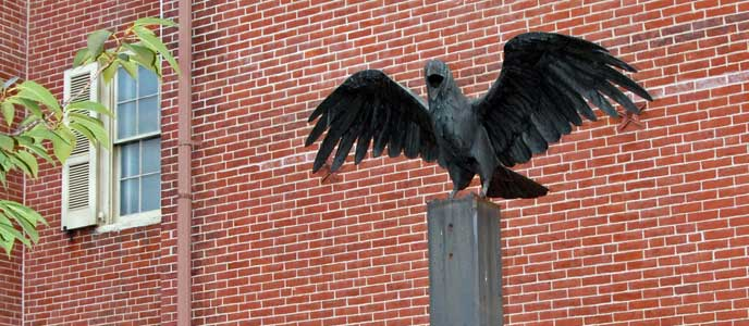 Color photo showing a large raven statue with wings outspread on a metal plinth in front of a red brick wall.