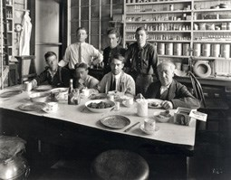 Thomas Edison sitting at a table with his assistants.  They are about to eat a meal.