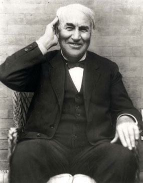 Thomas Edison holding his right hand to his right ear.