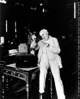 Edison with his motion picture projector in the library.