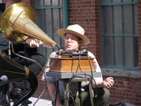 Curator Jerry Fabris checks the early phonograph during a wax cylinder recording.
