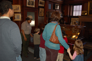 Family in Thomas Edison's library, listening to a Park Ranger present a program.