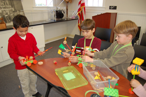 Children creating inventions using TinkerToys.
