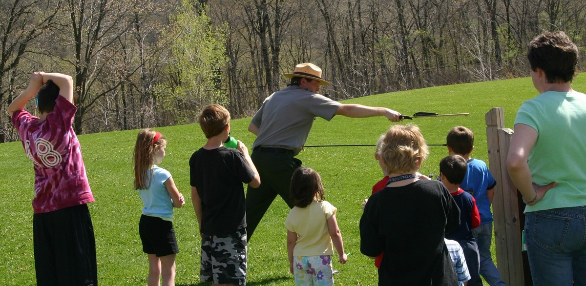 Ranger demonstrating ancient spear throwing device to school children
