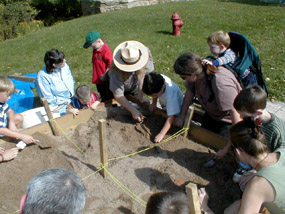 Children digging for artifacts in sandbox demonstration