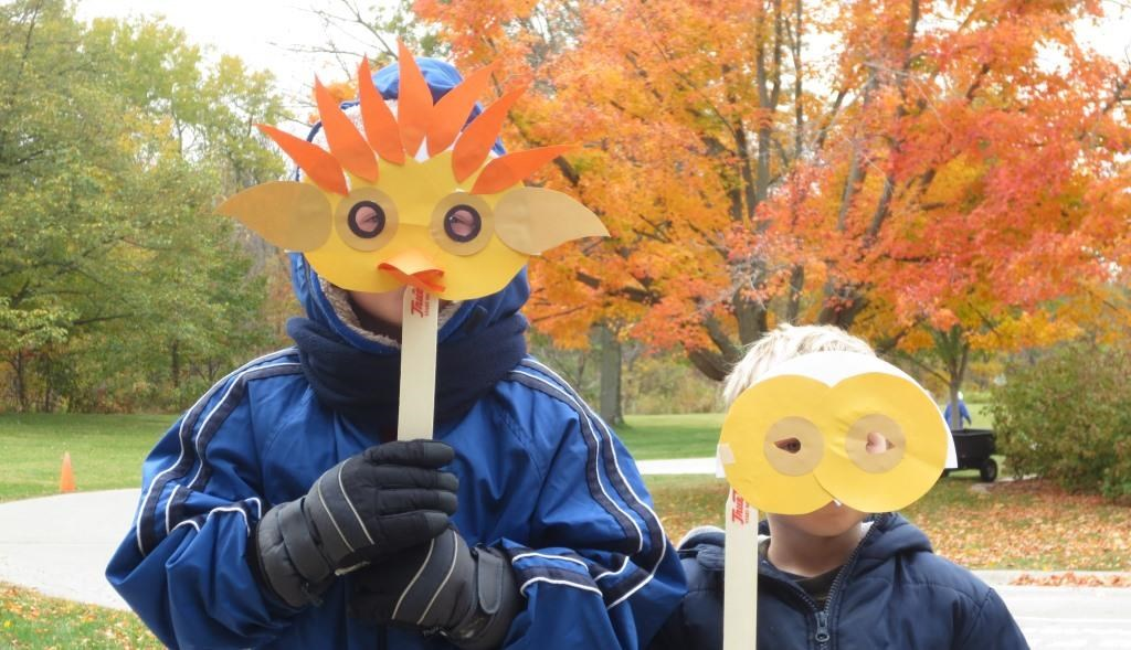 Two children holding paper masks in front of their faces.