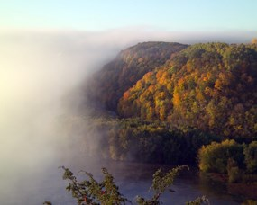 The foggy Mississippi River overlooked with bluff in full fall color.