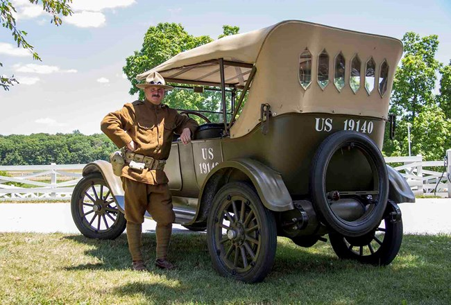 WWI solider standing next to car