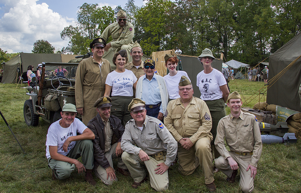 A group of World War II living historians pose for a picture with a World War II veteran. They are gathered around Jeep and camp tents are all around the group.