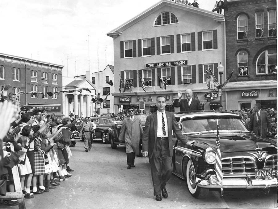 President Eisenhower being driven in his Chrysler Imperial limo greets onlookers in Gettysburg's Lincoln Square on November 14, 1955