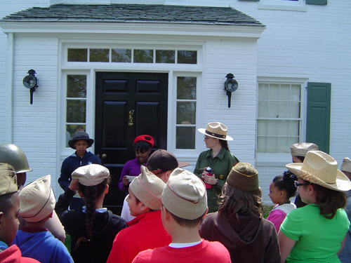 Students participating in the Eisenhower:Man of Many Hats program are welcomed to the Eisenhower home by the President and First Lady.