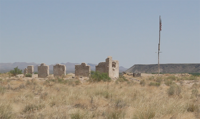 ruins of a fort with an American flag beside the ruins and a black mesa in the background