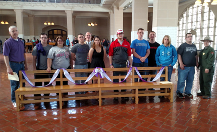 Hammondsport students and supporters stand with their bench in the Great Hall at Ellis Island.