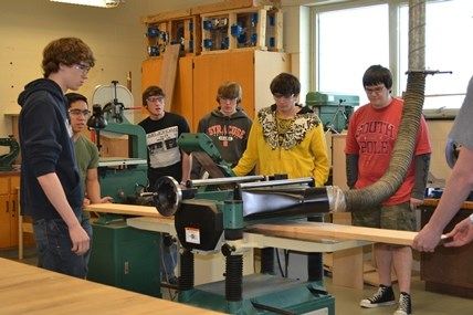 Seven Campbell-Savona High School students help to prepare lumber to be used as part of a replica bench.