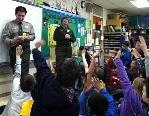 Park rangers in front of a 4th grade classroom with kids eagerly raising their hands.