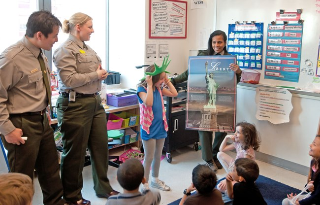 Two rangers visiting a local public school with students and desks in a classroom.